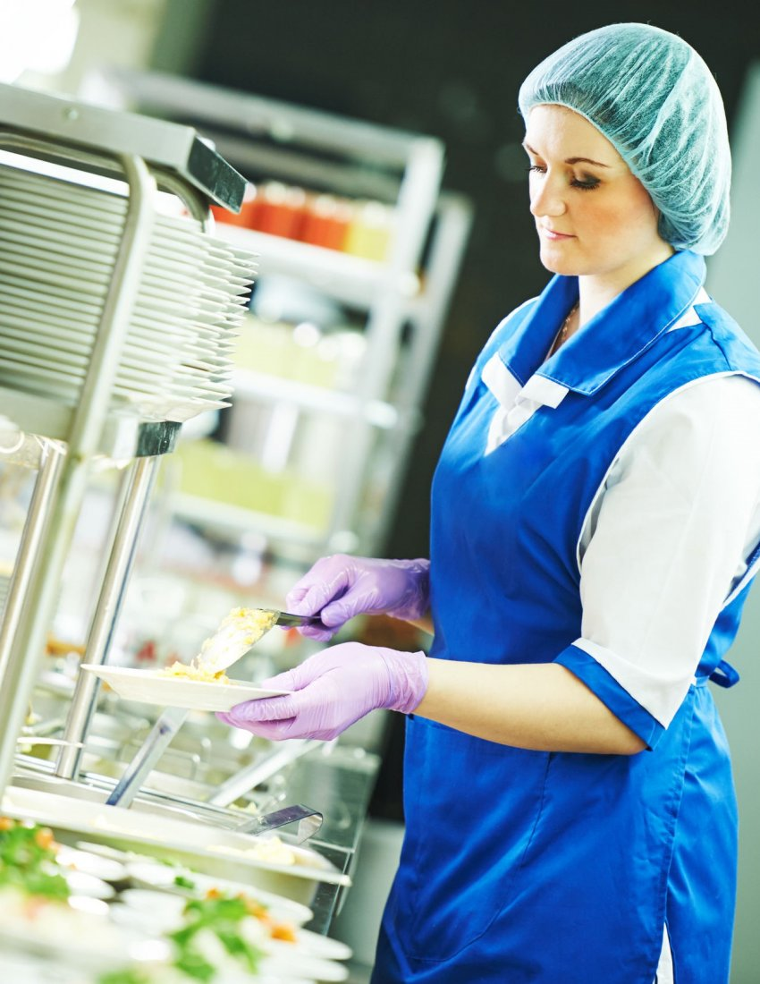 buffet female worker preparing and servicing food in cafeteria